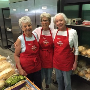 Three of the red apron volunteers at the South Portland Food Cupboard
